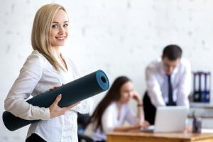 Büro, Mitarbeiterin mit Yoga-Matte blickt in die Kamera, im Hintergrund Kollegen am Bildschirm