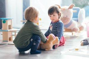 Kleiner Junge und kleines Mädchen spielen zu Hause mit Plüschtieren