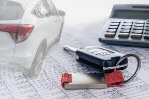 Tisch, Autoschlüssel liegen neben Taschenrechner auf ausgedruckten Zahlentabellen